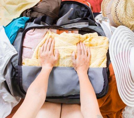 Photo pour Les mains de la femme emballent des vêtements dans un sac. Vue du dessus . - image libre de droit