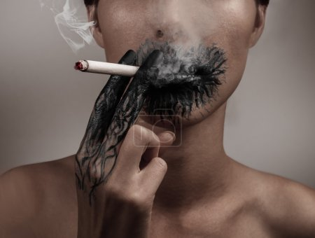 A woman smokes a cigarette, her hand and her mouth...