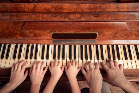 Family of three people is playing the piano, front view