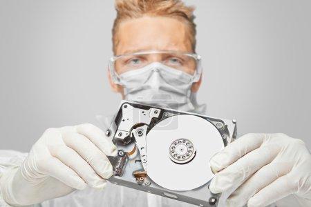 Foto de Técnico hombre de gafas y guantes muestra el disco duro - Imagen libre de derechos