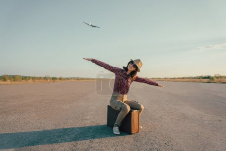 Photo for Happy traveler woman sits on vintage suitcase on road and makes a gesture of flight. With vintage retro instagram filter - Royalty Free Image