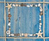 Rám lana a mušle na modré dřevěné pozadí