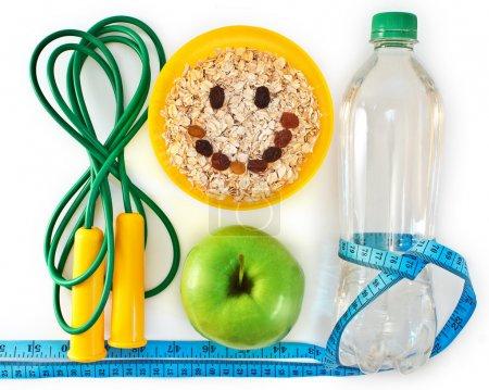 Photo pour Bouteille d'eau, muesli et pomme verte. Attributs d'un mode de vie sain - image libre de droit