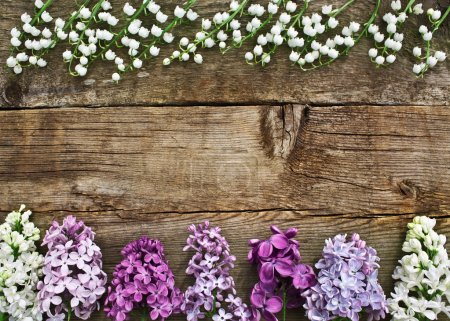 Lilies of the valley and lilac colored wooden texture. Unusual f