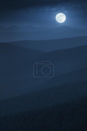 Photo pour Cette illustration photo montre un lever spacieuse et lumineux qui s'étend sur les crêtes de la montagne sans fin des forêts de montagne profondément en couches dans une tonalité de fin de nuit riche ton bleu, alors qu'un brouillard brumeux s'installe les vallées. - image libre de droit