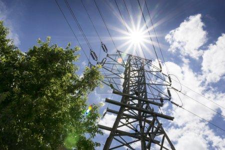 Foto de Estas líneas de alta tensión y la intensa luz del sol enfatizan los requisitos energéticos del verano con necesidades de electricidad para aire acondicionado y la generación de energía. - Imagen libre de derechos