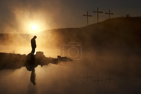 Morning Sunshine and Fog Surround Silhouetted Hiker On Calm Lake