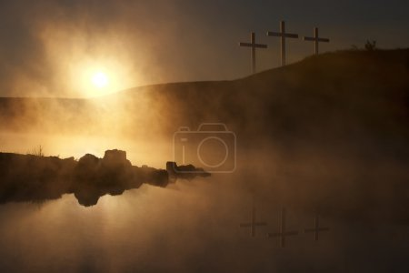 Foto de Dramática ilustración religiosa de la mañana del domingo de Pascua reflejando un momento de oración mientras un cálido sol se levanta sobre un lago de niebla, y tres cruces en una colina se reflejan en el agua debajo . - Imagen libre de derechos