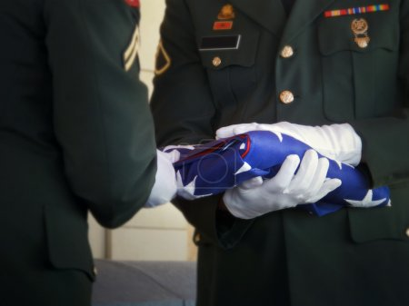 Military Honor Guard Folds United States Flag at Veteran Funeral