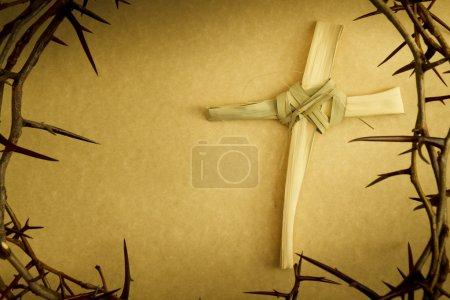Photo pour Cette croix à la main des feuilles de branche de palmier, entourée d'une couronne d'épines représente le dimanche des rameaux, crucifixion du vendredi Saint de Jésus et son lever le dimanche de Pâques - image libre de droit