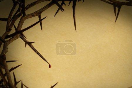 Foto de Esta corona de espinas con la gota de sangre contra papel pergamino representa la crucifixión de Jesús en la Cruz, muriendo y luego aumentando el domingo de Pascua. - Imagen libre de derechos