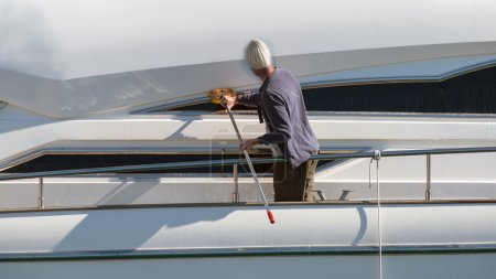 Male worker washing yacht
