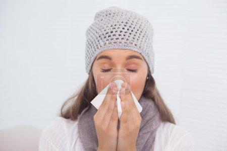 Photo pour Brune mignonne avec chapeau d'hiver sur le nez soufflant assis sur un canapé confortable - image libre de droit