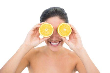 Photo pour Jolie brune tenant deux moitiés oranges sur ses yeux sur fond blanc - image libre de droit