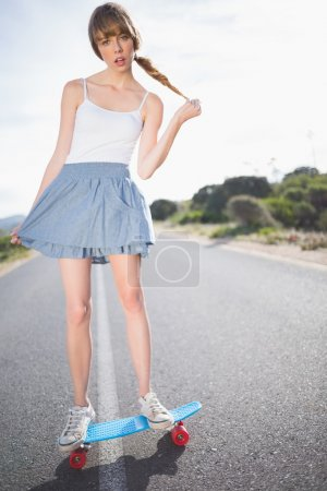 Trendy young woman balancing on her skateboard