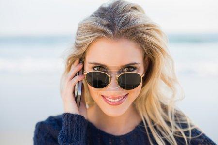 Photo pour Joyeux magnifique blonde au téléphone regardant par-dessus ses lunettes de soleil sur une belle plage sauvage - image libre de droit