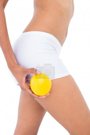 Close up of a fit woman holding an orange