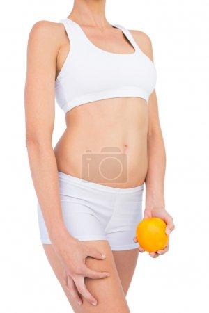 Photo pour Vue latérale de la femme en forme en tenue de sport tenant orange sur fond blanc - image libre de droit