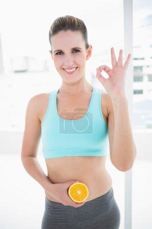Smiling model in sportswear holding orange slices on her belly