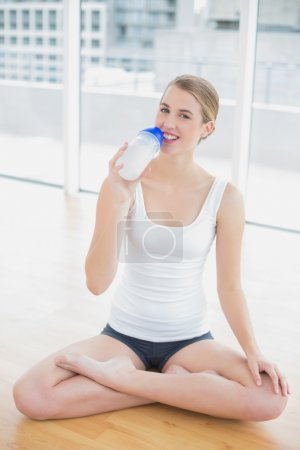 Smiling fit woman in lotus position holding flask