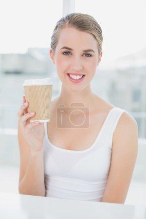 Smiling cute blonde holding mug of coffee
