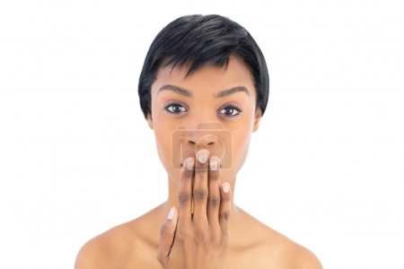 Serious black haired woman covering her mouth
