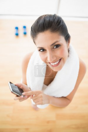 Fit woman using smartphone taking a break from workout smiling at camera