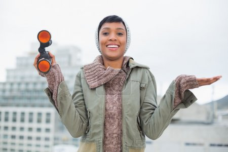 Pleased young model in winter clothes holding binoculars