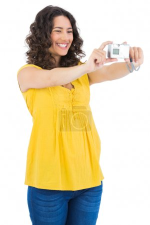Curly haired brunette taking picture of herself