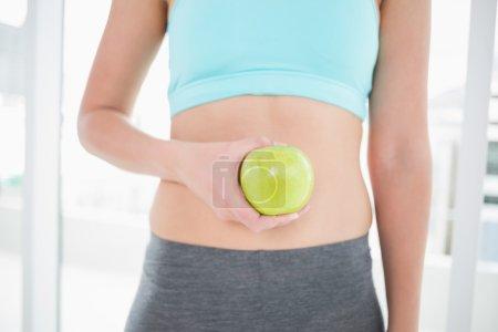 Woman in sportswear holding apple on her toned belly