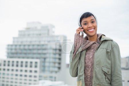 Photo pour Séduisant jeune modèle en vêtements d'hiver appeler quelqu'un avec son téléphone portable à l'extérieur par une journée nuageuse - image libre de droit