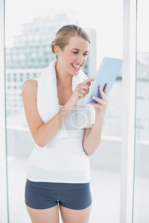 Happy sporty woman using tablet pc