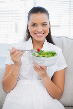 Smiling pretty woman eating healthy salad sitting on sofa