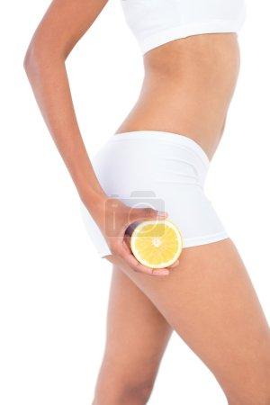 Photo pour Gros plan d'une femme en forme présentant la moitié d'une orange sur fond blanc - image libre de droit