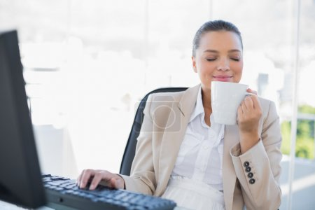 Smiling sophisticated businesswoman smelling coffee