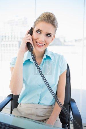 Cheerful stylish businesswoman answering the phone