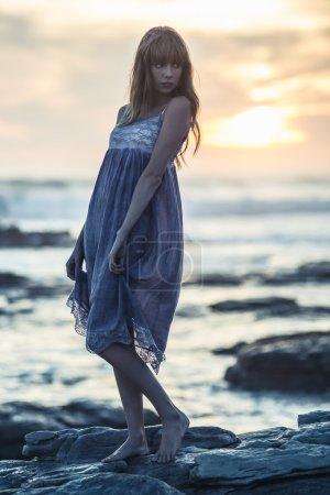 Beautiful model posing on rocks by the sea