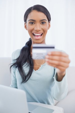 Smiling pretty woman using her laptop to buy online