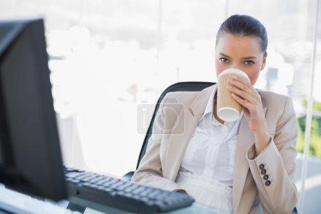 Foto de Pacífico sofisticada mujer de negocios beber café en la oficina brillante - Imagen libre de derechos