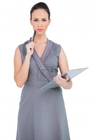 Pensive seductive model holding clipboard
