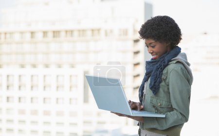Cheerful casual model using her laptop
