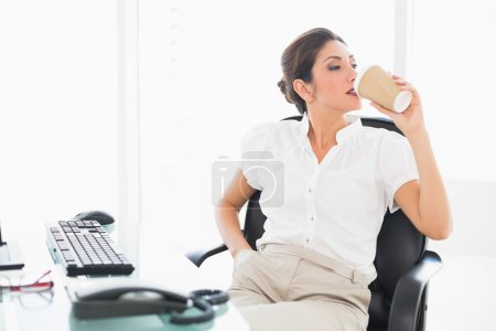 Photo for Relaxed businesswoman drinking a coffee at her desk in her workplace - Royalty Free Image