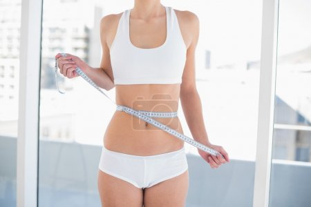 Photo for Close up of a thin woman in white sportswear measuring her waist - Royalty Free Image