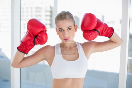 Dynamic young blonde model wearing boxing gloves