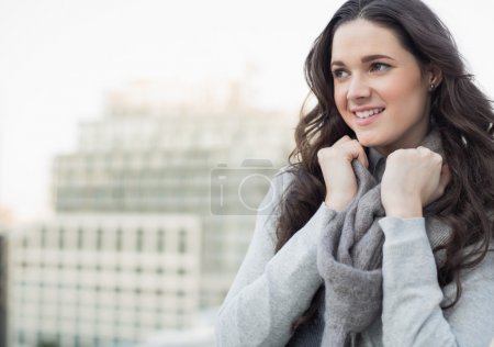 Photo for Smiling pretty woman in winter clothes posing outside on a cloudy day - Royalty Free Image