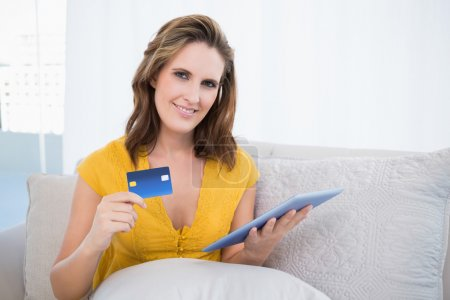 Pretty woman using her credit card to buy online