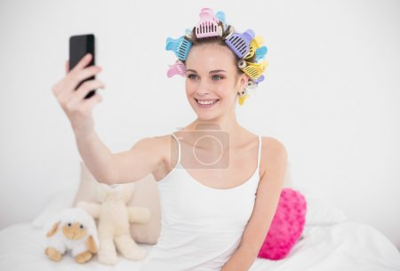 Pretty woman in hair curlers taking a picture