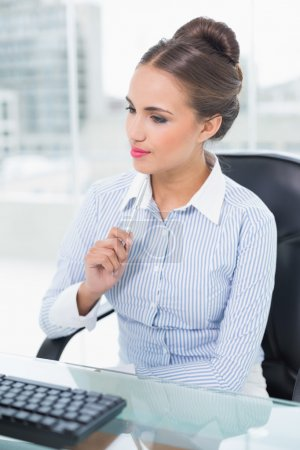 Thoughtful brunette businesswoman holding a pen