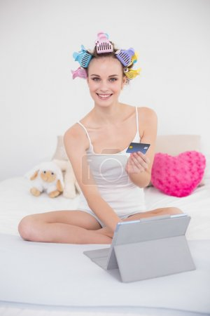 Pleased woman in hair curlers shopping online with her tablet pc