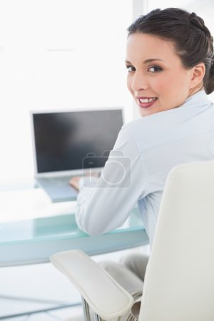 lächelnd stilvolle brünette Geschäftsfrau mit einem Laptop